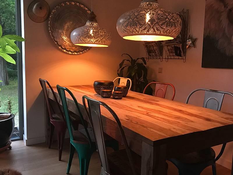 Grote witte open hanglamp boven eettafel