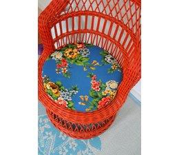 Fraaie rode rotan stoel met bloemkussen