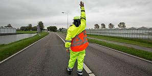 Verkeersregelaar op de weg met kleding van E-Veiligheidskleding/Uniwork
