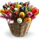 Houten tulpen in een rieten mand in gemengde kleuren