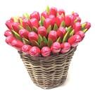 Roze houten tulpen in een rieten mand