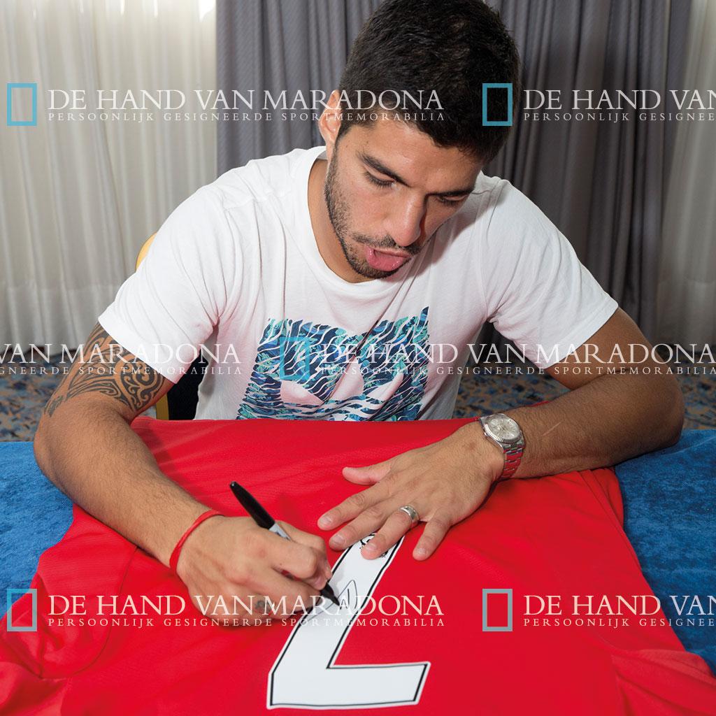 Suarez signeert shirts van Liverpool
