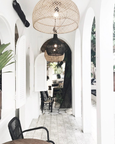 Magnifique pation avec un mix équilibré de lumière et de rotin. Photo par Hong Henwood Interior Designer