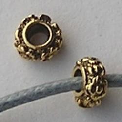 Metalen kraal met bloemetjes. Rondelle. Goudkleurig. 3.5x6.5mm. Per stuk voor.
