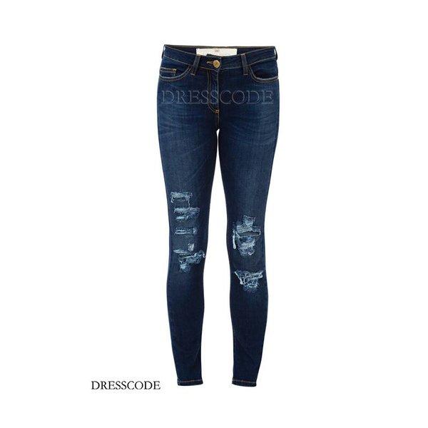 Jeans met scheuren en zwarte plaat met logo achter