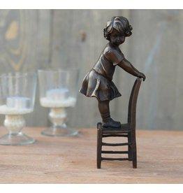 Mädchen, das auf Stuhl Bronze