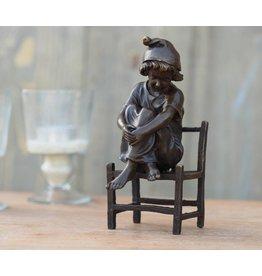 Eliassen Bildbronzemädchen, das auf einem Stuhl sitzt