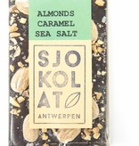 A bar of dark chocolate with almonds, caramel and seasalt