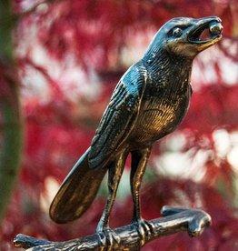 Vogel mit Beere im Mund auf Ast sitzend