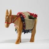 Desert Rose Donkey standing with saddle made of olivewood