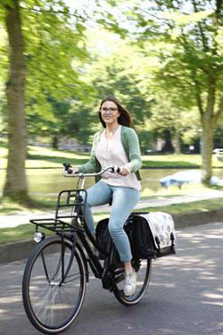 Dame op fiets met fietstassen