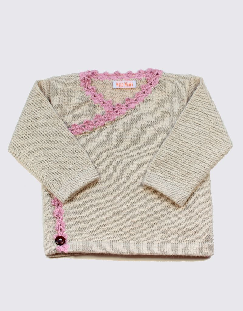 Alpaca crossover cardigan in soft white with pink crochet and wooden buttons.