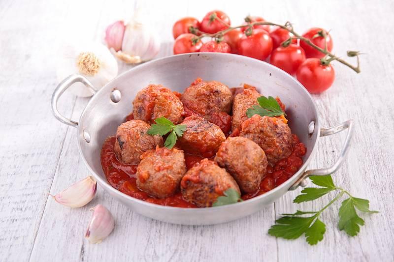 Gehaktballetjes in tomatensaus, gekookte aardappelen met jus en bospeen met tuinboontjes in room