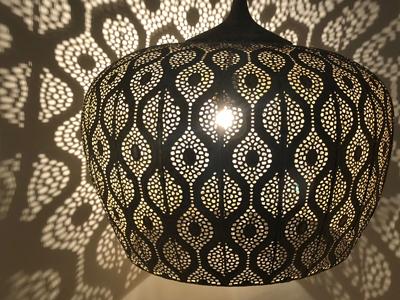 Prachtige licht patronen op de muur van de open filigrain hanglamp