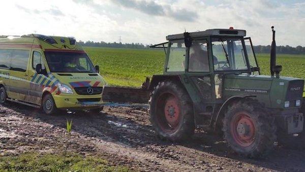 Ambulance door tractor uit modder geholpen