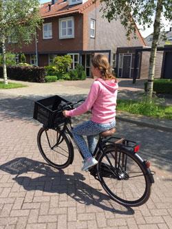 Meisje op fiets met fietskrat